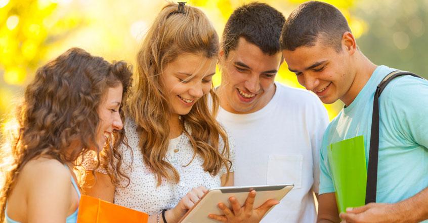 4 junge Menschen betrachten ein Ipad